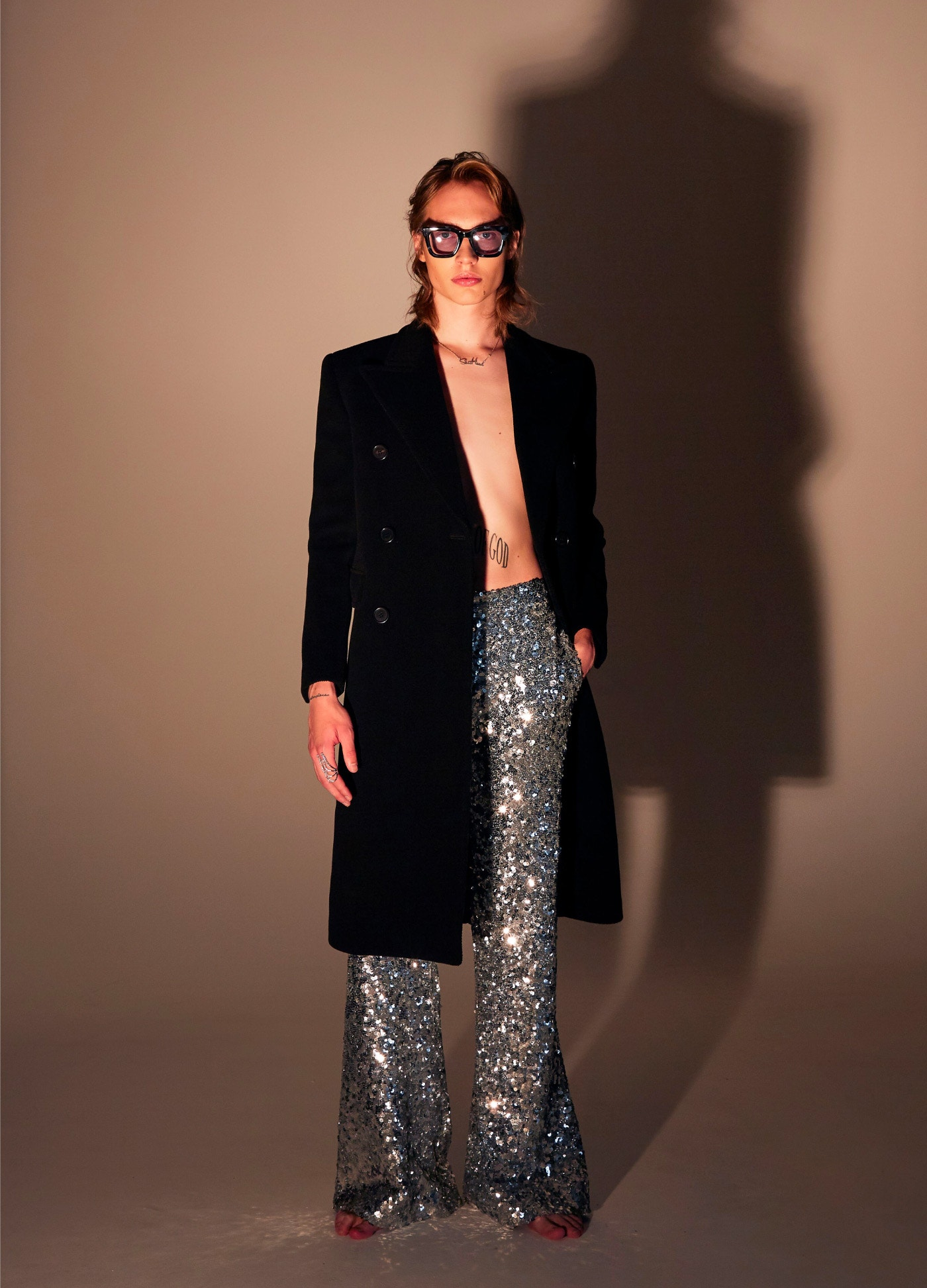 SAINT LAURENT Double-Breasted Overcoat – HALPERN Sequin Trousers – SACAI Sunglasses – YEPREM Ring