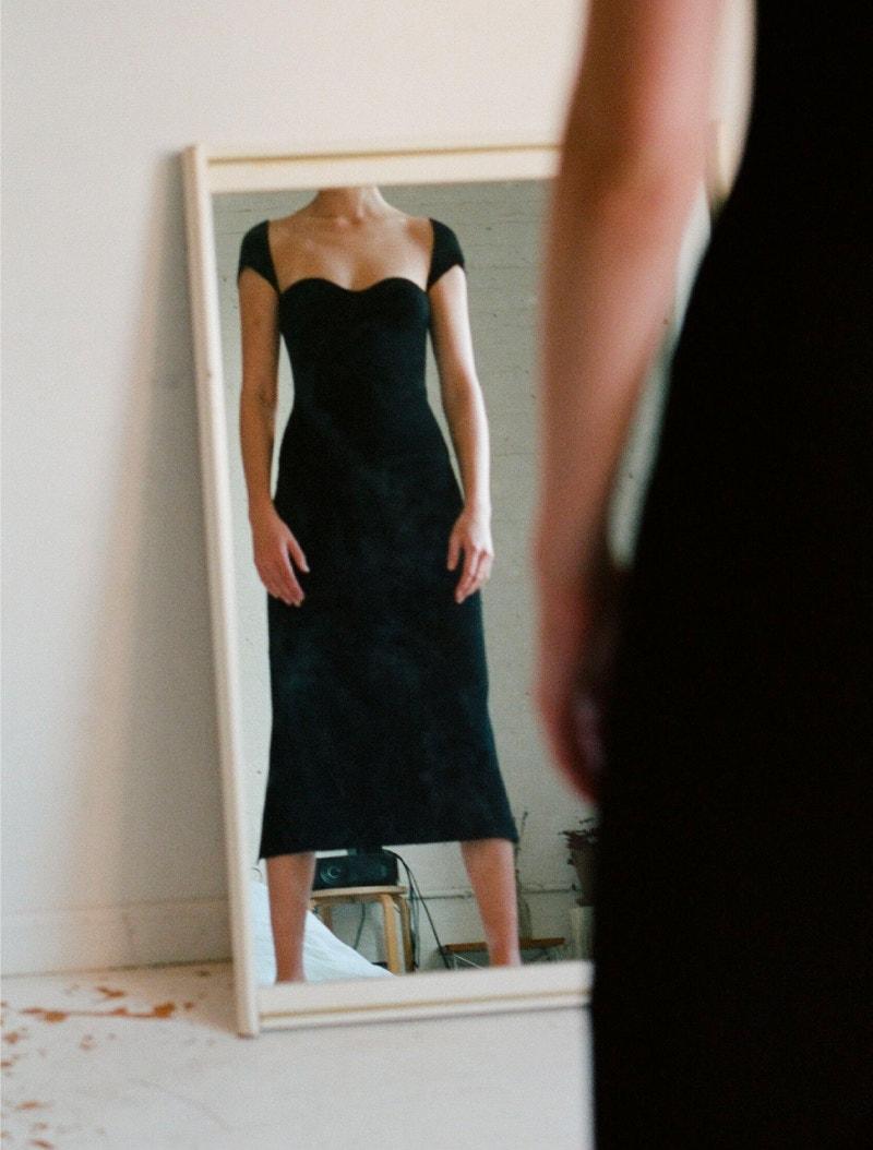 model wearing black khaite allegra dress
