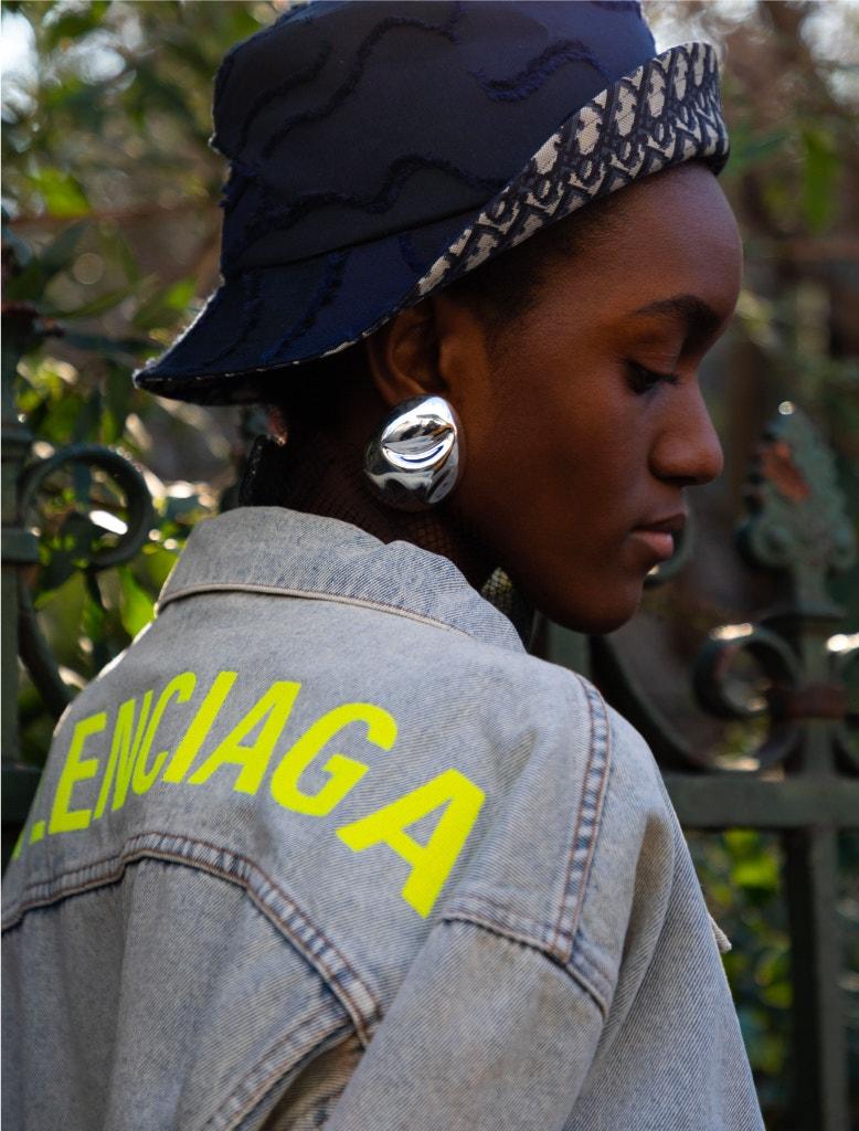 model wearing balenciaga denim jacket, dior bucket hat, and monica sordo earrings